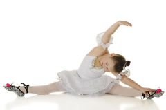 Graceful Stretch. A young elemantary ballerina gracefully stretching in her dance costume.  On a white background Royalty Free Stock Image