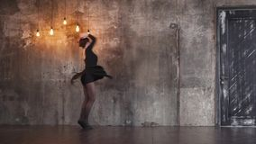Trained dancer girl is swirling in a dramatic dance in a dark gothic hall