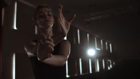 Graceful woman ballerina in a dark dress on a dark stage of the theater in the smoke performs dance moves in slow motion.  stock video
