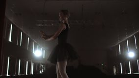 Graceful woman ballerina in a dark dress on a dark stage of the theater in the smoke performs dance moves in slow motion.  stock footage