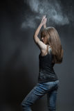 Graceful woman dancing in the cloud of dust. Girl in flour, gray background Stock Photography
