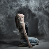 Graceful woman dancing in the cloud of dust. Girl in flour, gray background Royalty Free Stock Images