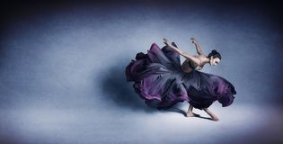 Graceful woman dancing in flowing dark blue dress royalty free stock photo