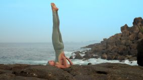 Woman does shoulder stand in rocky sea coast slow motion. Graceful woman in grey does supported shoulder stand on rocky sea coast in early morning against blue stock video