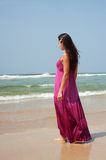 Graceful woman in long dress. Walking at the beach Stock Photos