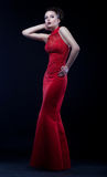 Graceful woman in modern long dress posing. Beautiful bride in beauty red fashion dress - podium model Stock Images