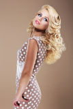 Graceful Woman in Retro Polka Dot Dress Looking Back Royalty Free Stock Photography