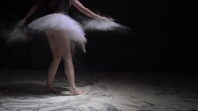 Graceful woman in tutu throwing dust in the dark. Graceful woman in ballet tutu throwing white dust and jumping in the dark room video stock footage