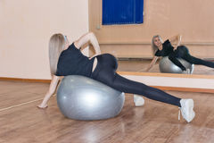Graceful young girl does fitness exercises on an exercise ball Stock Image