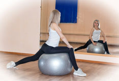 Graceful young girl does fitness exercises on an exercise ball Royalty Free Stock Images