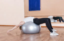 Graceful young girl does fitness exercises on an exercise ball Royalty Free Stock Photo