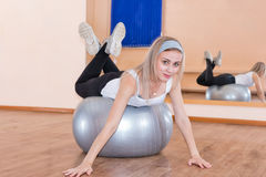 Graceful young girl does fitness exercises on an exercise ball Royalty Free Stock Image