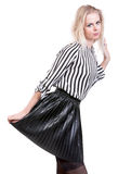 Graceful young girl posing. Isolation on a white background. Young beautiful blonde girl in a striped blouse and skirt posing on an isolated white background Stock Images