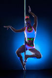 Graceful young pole dancer with fluorescent makeup. Posing on blue background Stock Photos