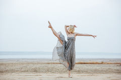Graceful young woman dancer dancing on the beach. Graceful young woman dancer in beautiful dress dancing on the beach Stock Photography