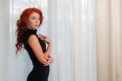Graceful young woman in short black dress. Standing near window with white curtains Royalty Free Stock Photography