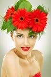 Gracefull ung kvinna med röda blommor i henne hår Royaltyfri Fotografi