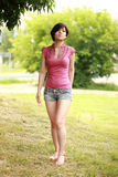 Gracefully korean walking to camera, smiling. Beautiful brown in full growth stay on the grass in the city park, pink dress and jeans shorts. Background a tree Stock Image