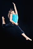 Gracefulness. Young woman in tracksuit jumping on black background Stock Image