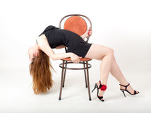 Gracefulness. Portrait of a girl with long hair on a chair Royalty Free Stock Images