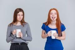 Gracejo dois feliz e jovens mulheres olhando de sobrancelhas franzidas tristes que bebem o chá foto de stock