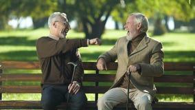 Gracejo masculino idoso com amigo, anciões que têm o divertimento no parque do verão, aposentadoria video estoque