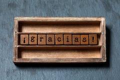 Gracias Danke in der spanischen Übersetzung Weinlesekasten, hölzerne Würfelphrase mit im altem Stil Buchstaben Grauer Stein gemas lizenzfreies stockfoto