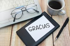 Gracias, Motivational Words Quotes Concept. Gracias Spanish thank you words letter, written on piece of memo paper, work desk top view. Motivational business stock photo