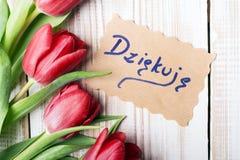 Gracias para cardar (dziÄ™kujÄ™ polaco de la palabra) y el ramo del tulipán Fotografía de archivo libre de regalías