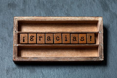 Gracias. Thank you in Spanish translation. Vintage box, wooden cubes phrase with old style letters. Gray stone textured. Background. Close-up, up view, soft royalty free stock photo