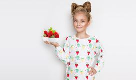 Gracious little girl with blond hair and blue eyes standing on a white background wearing a sweatshirt and a strawberry Stock Images