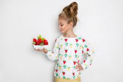 Gracious little girl with blond hair and blue eyes standing on a white background wearing a sweatshirt and a strawberry Stock Photos