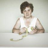 Gracious senior lady portrait with apple royalty free stock photo