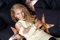 Gracious small a young girl with amazing eyes and blond hairs lies on the bed and Royalty Free Stock Photo