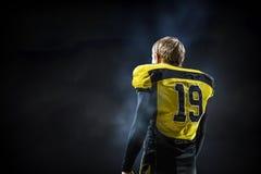 Gracz futbolu na ciemnym tle Mieszani środki Zdjęcie Stock