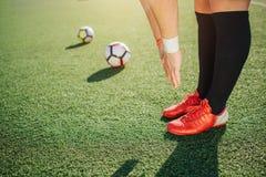 Gracz futbolu stojak zielenieć pole na gazonu i rozciągania puszku Utrzymuje nogi i ręki wpólnie Dwa futbolowej piłki obraz royalty free