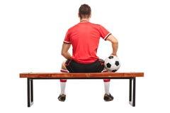 Gracz futbolu trzyma obsiadanie na ławce i piłkę Fotografia Royalty Free
