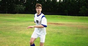 Gracz futbolu uderza piłkę w polu zbiory