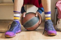Gracz koszykówki trzyma piłkę f w szatni na ławce zdjęcie royalty free