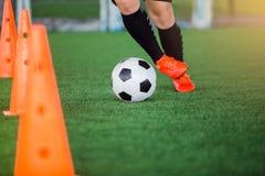 Gracz piłki nożnej jogging z oklepa i kontroli futbolem między szyszkowymi markierami obraz stock