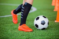 Gracz piłki nożnej jogging z oklepa i kontroli futbolem między szyszkowymi markierami fotografia royalty free