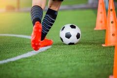 Gracz piłki nożnej jogging z oklepa i kontroli futbolem między szyszkowymi markierami obraz royalty free