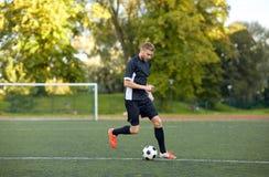 Gracz piłki nożnej bawić się z piłką na boisku piłkarskim Obraz Royalty Free