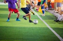 Gracz piłki nożnej bieg łapać w pułapkę piłkę dla krótkopędu i kontrolować cel z chirliderka drużyny tłem obrazy stock