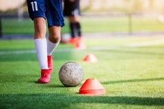 Gracz piłki nożnej jogging i kontrolna piłka między szyszkowymi markierami dla piłki nożnej szkolenia fotografia royalty free