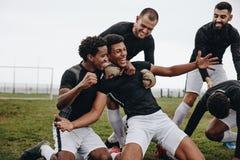 Gracz piłki nożnej robi kolanowemu obruszeniu po zdobywać punkty cel obrazy stock