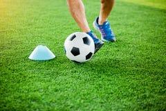 Gracz piłki nożnej stawiający błękitni sportów buty jogging z oklepa i kontroli futbolem między szyszkowymi markierami obraz royalty free