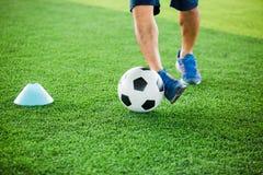 Gracz piłki nożnej stawiający błękitni sportów buty jogging z oklepa i kontroli futbolem między szyszkowymi markierami obrazy royalty free