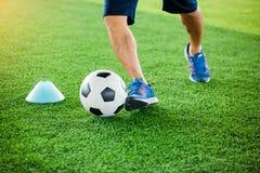 Gracz piłki nożnej stawiający błękitni sportów buty jogging z oklepa i kontroli futbolem między szyszkowymi markierami zdjęcia stock