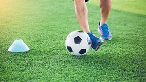 Gracz piłki nożnej stawiający błękitni sportów buty jogging z oklepa i kontroli futbolem między szyszkowymi markierami obraz stock